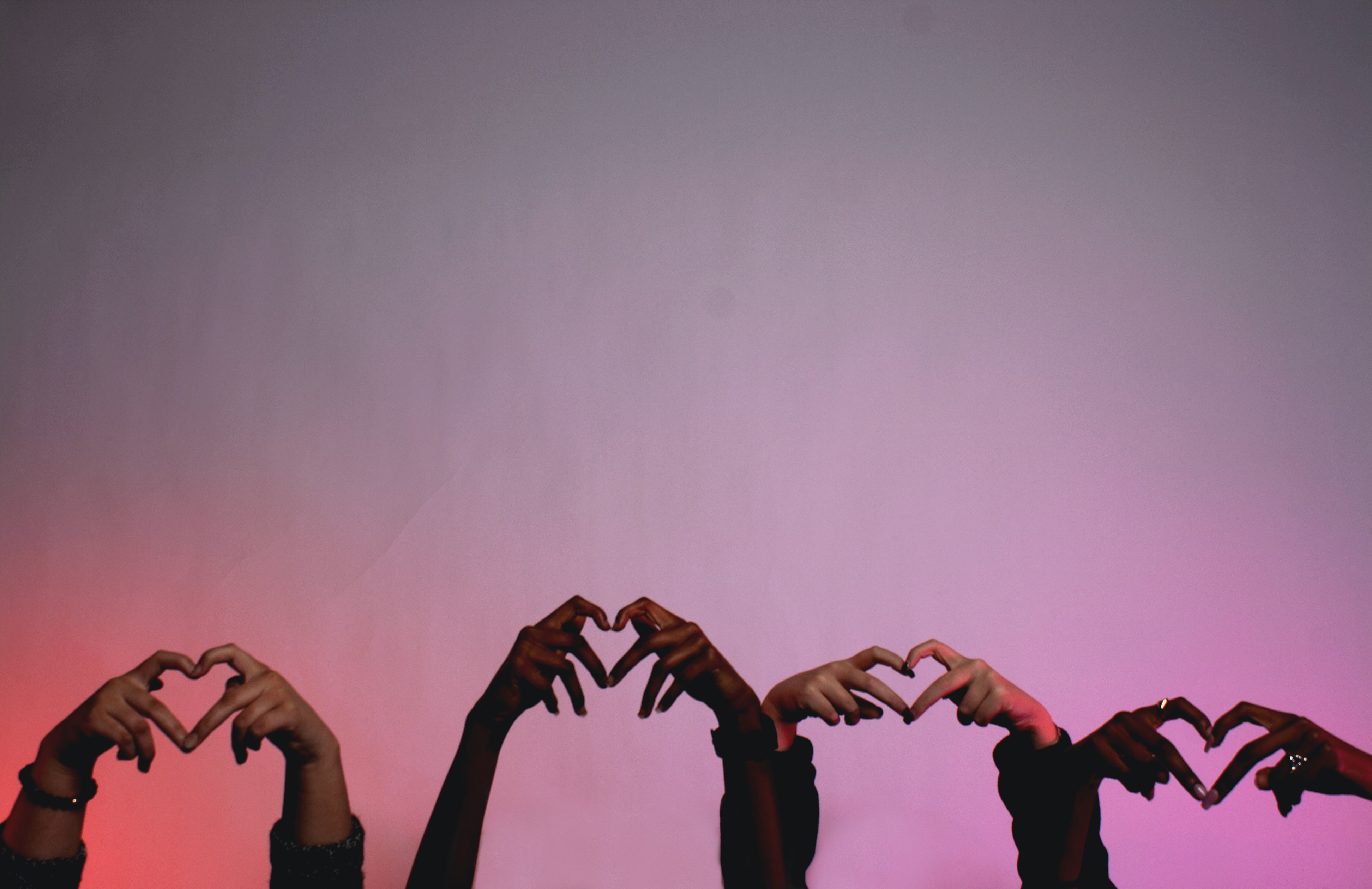 Hands in air in shape of hearts